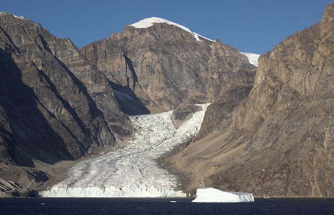 Tidewater Valley glacier on the shore of Nordvest Fjord, the glacier is split by a rocky outcrop. East Greenland.