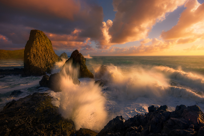 A dynamic scene on the Oregon coast, with crashing waves illuminated by warm sunset light.<br />