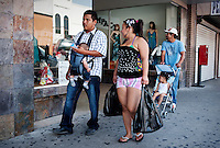 Shoppers walk along Main Street in downtown McAllen, Texas, Sunday, April 4, 2010. Downtown McAllen stores don't sell designer or name brand items, but still reach a wide customer base for McAllen residents and visiting Mexican tourists. ..PHOTO/ Matt Nager