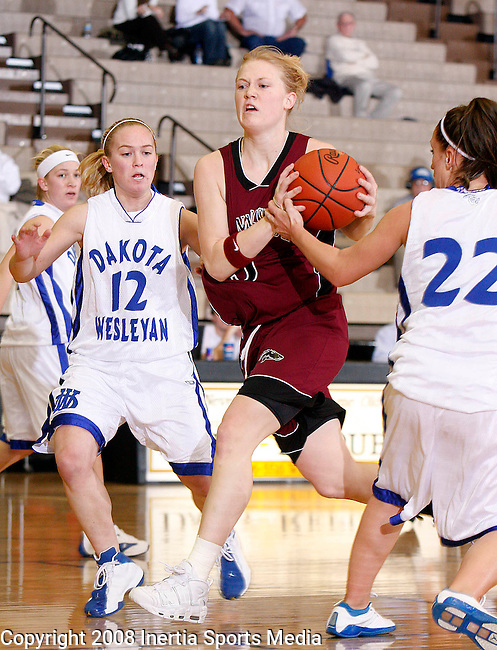 MITCHELL, SD - FEBRUARY 6 -- Dani Gass #3 of Morningside drives through Dakota Wesleyan defenders Ashley Johnson #12 and Sarah Mortenson #22 in the first half of their game Wednesday evening at the Corn Palace.