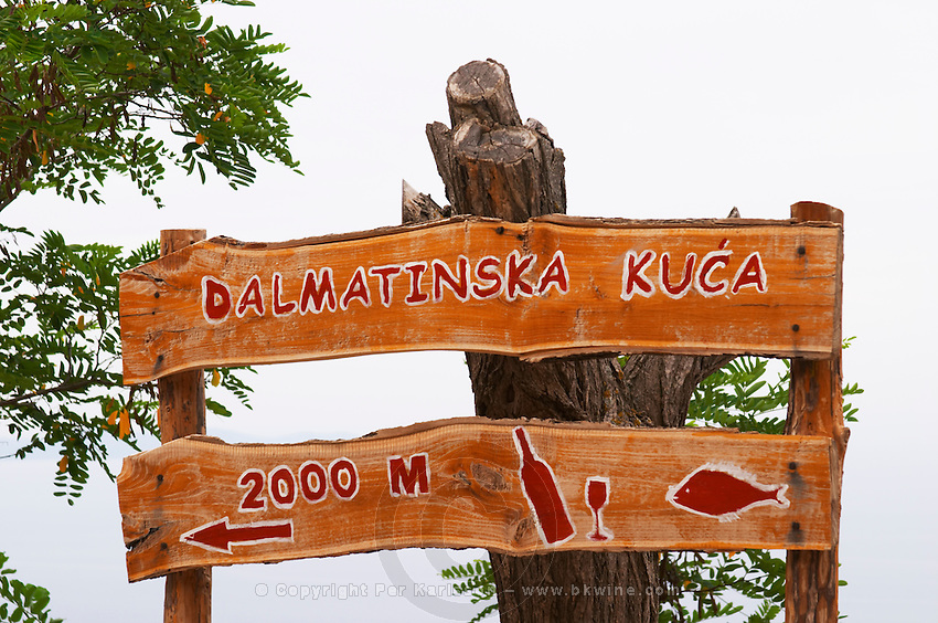 Wooden sign saying Dalmatinska Kuca 2000 m advertising a restaurant with Dalmatian kitchen. Bottle of wine and glass and a fish. Potmje village, Dingac wine region, Peljesac peninsula. Dingac village and region. Peljesac peninsula. Dalmatian Coast, Croatia, Europe.