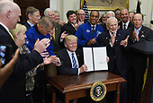 United States President Donald J. Trump, signs an Executive Order to reestablish the National Space Council as Apollo 11 astronaut Buzz Aldrin (R) looks on  in the Roosevelt Room of the White House in Washington, DC, on June 30, 2017. a<br /> Credit: Olivier Douliery / Pool via CNP