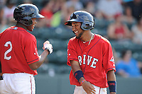 Second baseman Wendell Rijo (11) of the Greenville Drive is congratulated by Manuel Margot after scoring a run in a game against the Augusta GreenJackets on Sunday, July 13, 2014, at Fluor Field at the West End in Greenville, South Carolina. Rijo is the No. 18 prospect of the Boston Red Sox, according to Baseball America. Greenville won, 8-5. (Tom Priddy/Four Seam Images)