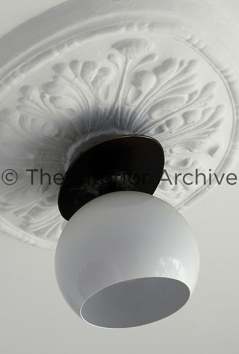 In the living room a 1970s glass globe has been attached to a metal plate and converted into a lightshade