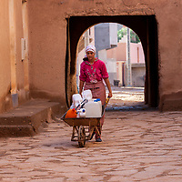 Ksar Elkhorbat, Morocco.  Young Woman Bringing Water in her Wheelbarrow into the Casbah.