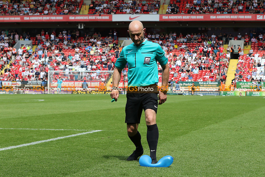 Referee Roger East, bursts one of the balloons thrown onto the pitch by the crowd during Charlton Athletic vs Burnley, Sky Bet Championship Football at The Valley on 7th May 2016