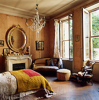 A traditional yellow bedroom with a high ceiling wooden floor. A gilt oval mirror hangs above a carved fireplace and a double bed is covered with layers of quilts.