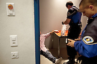Switzerland. Geneva. A cell at the Paquis police station. A police officer is collecting the belongings of a prisoner in a plastic bag. The man was arrested under the heavy influence of alcohol. The inmate is from South America. He is drunk and seats on the floor. A police station or station house is a building which serves for police officers. The building contains temporary holding cells and interview/interrogation rooms. Both policemen are wearing a ballistic vest, bulletproof vest or bullet-resistant vest which is an item of personal armor that helps absorb the impact from knives, firearm-fired projectiles and shrapnel from explosions, and is worn on the torso. Soft vests are made from many layers of woven or laminated fibers and can be capable of protecting the wearer from small-caliber handgun and shotgun projectiles, and small fragments from explosives such as hand grenades. 24.03.12 © 2012 Didier Ruef