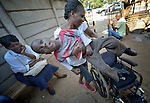 Eric Lovemore, 8, gets placed in his wheelchair at his house in Bulawayo, Zimbabwe, by his stepmother, Zandile Tohori. Lovemore suffered cerebral palsy and uses a wheelchair provided by the Jairos Jiri Association with support from CBM-US.