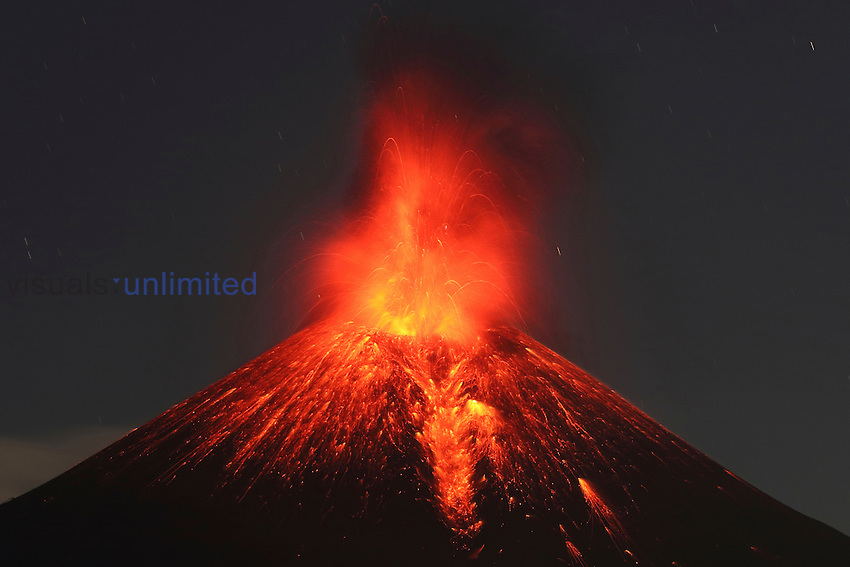Momotombo Volcano erupting at night with glowing lava bombs and ash cloud, Nicaragua.