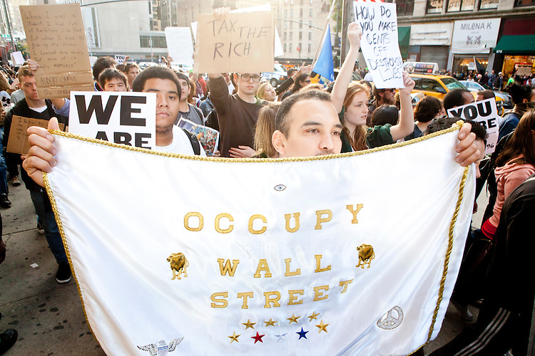 """Thousands of people march up 6th Avenue to Times Square on October 15, 2011 in New York City in support of the """"Occupy Wall Street"""" movement."""