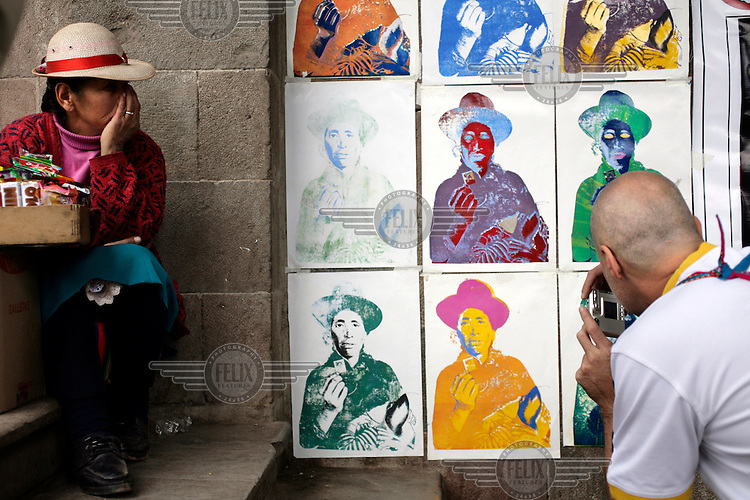 An Inca woman, with a simple sweet stall, watches as a tourist photographs an 'Andy Warhol-style' poster of an Inca woman that is taped to a wall next to her plot.