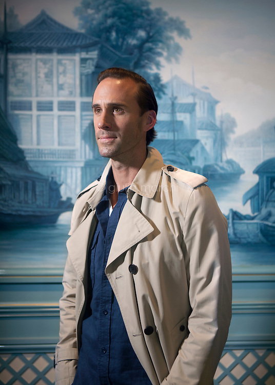 British actor Joseph Fiennes poses for a portrait in front of a Chinese landscape painted on a wall of the Ritz-Carlton in Tianjin, China after the announcement of plans for the film The Last Race.