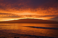 Surfers enjoy a colorful sunrise at McGregor Point, Maui.