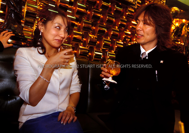 10/10/2002--Tokyo, Japan..Just like at the female hostess bars, the male hosts duties are to pour drinks, flirt and flatter with guests. Here, at the 'Lady's Club', a host and guest engage in flirtatious banter...All photographs ©2003 Stuart Isett.All rights reserved.