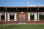 Modern wooden church with crucifix cross and sign saying 'no ball games' at Kessingland, Suffolk, England