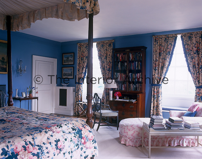 A guest bedroom is painted a soft blue, a colour reflected in the chintz used for the bed hangings and curtains