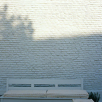 Shadows play on a white brick wall that forms the backdrop for a bench on a terrace in Athens