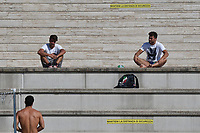 Mattia Zuin ( bottom), Stefano Di Cola and Gabriele Detti, talk, respecting the social distancing, before the start of a training session. Some adhesive stripes reading ' respect the safety distance ' have been put on the wall and on the steps to comply the security measures decided by italian swimming federation . <br /> Italian athletes were able to resume training last week after more than 50 days of lockdown due to the coronavirus (covid-19) pandemic <br /> Roma 12-5-2020 Centro Federale di Ostia <br /> Photo Andrea Staccioli / Deepbluemedia / Insidefoto