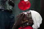 KINSHASA, DEMOCRATIC REPUBLIC OF CONGO APRIL 23: Moguy Longome, age 52, and suffering from cataracts, has holy water poured in her eyes at ?Ebale Mbonge? on April 23, 2006 in central Kinshasa, Congo, DRC. She has prayed here for a month, after seeing a medical doctor. A friend told her that she could get cured here. It?s a spiritual place where members come to get cured from bad and evil spirits. Many are suffering from different diseases and they hope to get cured while getting treatment. Kinshasa, a city of about eight million people is battling with bad infrastructure and no public transport. Congo, DRC is in ruins after forty years of mismanagement by the corrupt dictator and former president Mobuto Sese Seko. He fled the country in 1997 and a civil war started. The country is planning to hold general elections by July 2006, the first democratic elections in forty years.(Photo by Per-Anders Pettersson)