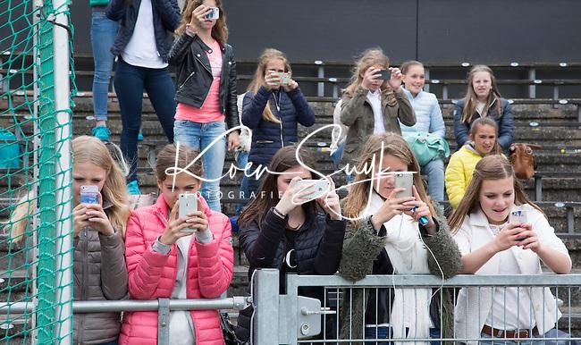 AMSTELVEEN - Supporters, klasgenoten, medescholieren maken opnames met hun smartphone. NK Schoolhockey. De finale in de categorie Meisjes Jong ging tussen Het Willem de Zwijger College uit Bussum (rode shirts)  en het Koning Willem II college uit Tilburg. Winnende team en kampioen werd  Willem de Zwijger College uit Bussum. © 2015 Koen Suyk