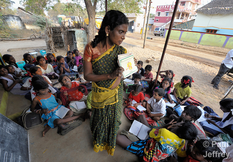 Teacher Vengatammal helps children study in an after-school tutoring program in Poonthandalam, a village in the southern India state of Tamil Nadu.