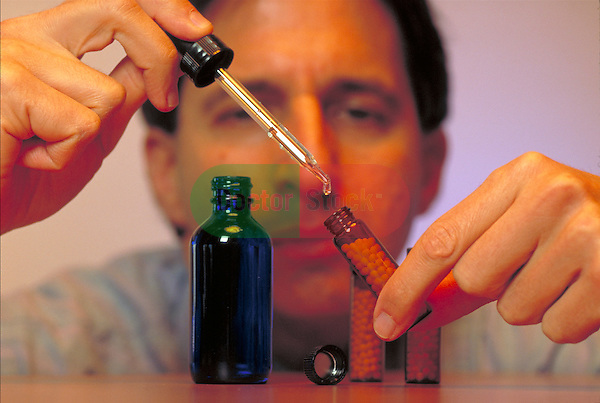 homeopathic herbalist dropping medicinal concentrate into dispensing vial