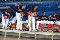 Batavia Muckdogs outfielder CoCo Johnson (49), catcher Chad Wallach (55) and infielder Avery Romero (13) work their way down the dugout after it flooded during a brief but heavy rain storm during a game against the Hudson Valley Renegades on August 8, 2013 at Dwyer Stadium in Batavia, New York.  The game was called due to unplayable field conditions.  (Mike Janes/Four Seam Images)