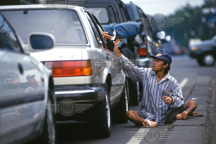 Indonesia, Jakarta..Health. Poverty. Cripled man begging at traffic lights receiving small change from a man driving an expensive car..©Mark Henley