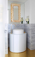 In the luxurious master bathroom, the cabinets are custom-made and the floor is sheathed in glass mosaic tiles by Studium.