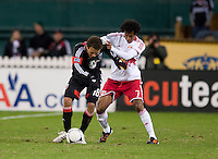 Nick DeLeon (18) of D.C. United fights for the ball with Roy Miller (7) of New York Red Bulls during the game at RFK Stadium in Washington DC. D.C. United tied New York Red Bulls, 1-1.