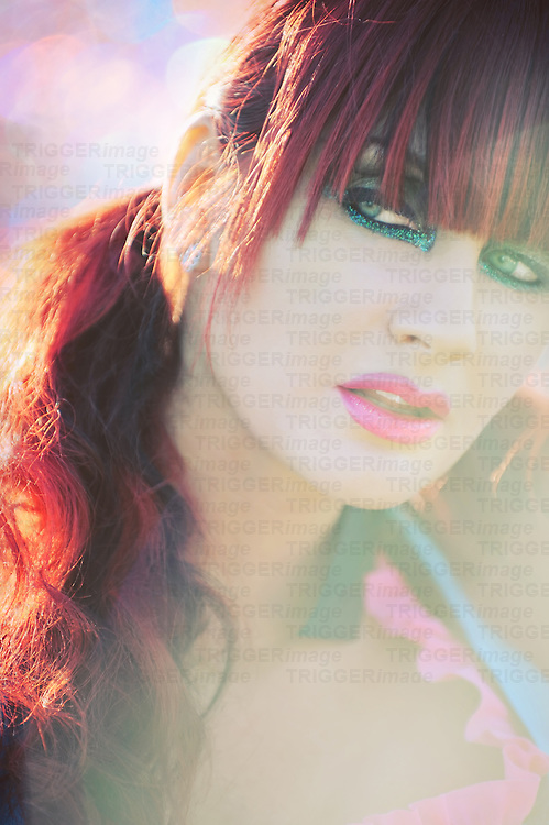 A woman with colorful red pigtails and funky makeup gazes wickedly off to the side.
