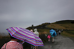 Tourists carry colorful umbrellas as they brave wind and rain as they walk along the Cliffs of Moher on the west coast of Ireland.
