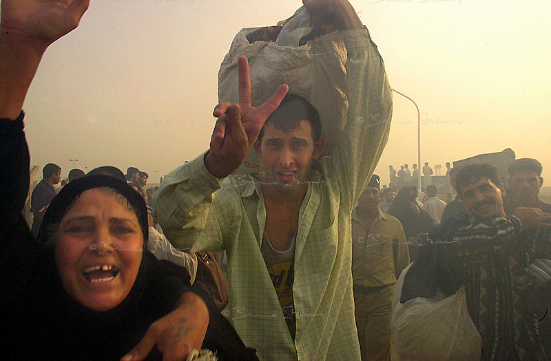 Abu Graibh penitentiary, near Baghdad, October 20, 2002.Tens of thousands of prisoners are amnistied by president Saddam Hussein and are released 2 hours after the official announcement..Prisoners rushing out of the compound with their possessions.