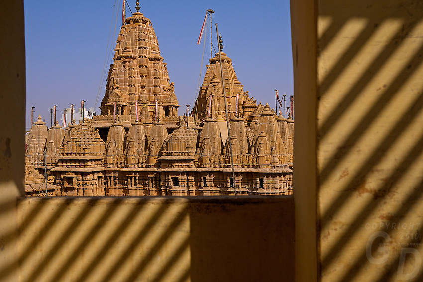 """View of the main Jain temple from a window across the road. Jaisalmer, the """"Golden City,"""" is located on the westernmost frontier of India in the state of Rajasthan. Close to the Pakistan border, the city is known for its proximity to the Thar Desert.<br /> <br /> The city is dominated by the Jaisalmer Fort, also known as Sonar Qila (Golden Fort). Unlike most forts in India, the Jaisalmer Fort is a living fort. There are shops, hotels and age old havelis (homes) inside the fort area where families have lived for generations."""