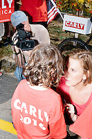A press videographer records video while Republican presidential candidate Carly Fiorina greets a young supporter before marching in the Labor Day parade in Milford, New Hampshire. Republican candidates John Kasich, Carly Fiorina, and Lindsey Graham, and Democratic candidate Bernie Sanders marched in the parade.