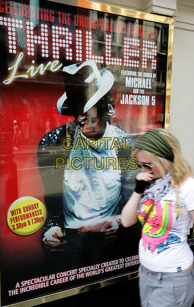 "ATMOSPHERE .Michael Jackson dies at the age of 50 after suffering a heart attack on July 25th, 2009 .A fan cries while passing The Lyric Theatre where the musical ""Thriller"" is playing in London's West End, England..June 26th, 2009.gv general view half length poster crying tears sunglasses shades glove hair band white t-shirt .CAP/CAM.©Andre Camara/Capital Pictures."