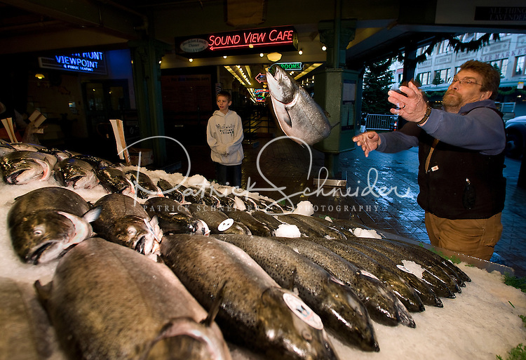 A worker throws a salmon at Pike Place Market in Seattle Washington.