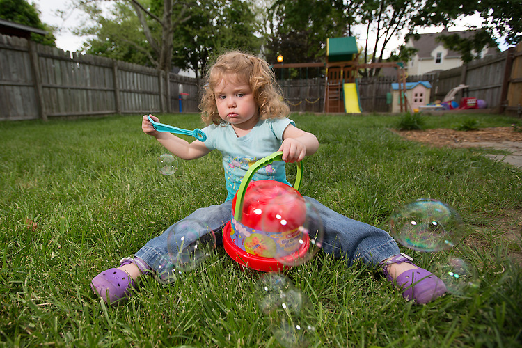 Katelyn blows bubbles in the backyard. The bubbles were a present for her third birthday.