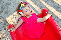 A pretty little girl with flowers having fun