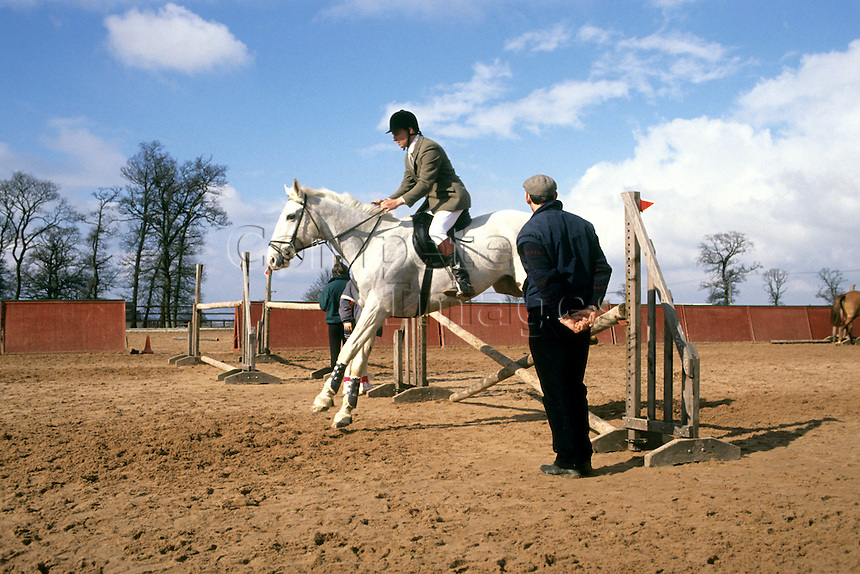 Man jumping his horse during a lesson