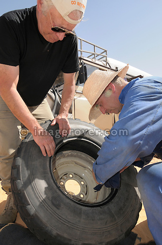 Africa, Tunisia, nr. Tembaine. Siegfried and Gernot repairing a flat tyre in the desert on a historic Series 3 Land Rover Dormobile. --- No releases available, but releases may not be needed for certain uses. Automotive trademarks are the property of the trademark holder, authorization may be needed for some uses.  --- Info: Image belongs to a series of photographs taken on a journey to southern Tunisia in North Africa in October 2010. The trip was undertaken by 10 people driving 5 historic Series Land Rover vehicles from the 1960's and 1970's. Most of the journey's time was spent in the Sahara desert, especially in the area around Douz, Tembaine, Ksar Ghilane on the eastern edge of the Grand Erg Oriental.
