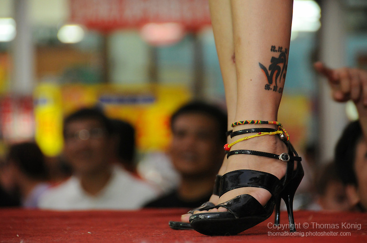 Bao-Jhong Yi-min Temple, Kaohsiung -- Tattooed legs of a pole dancer at the annual 'Divine Pig' (Shen Zhu) festival during Ghost Month.