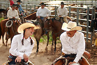 Tori Townsend and Efrain Corrales, both workers at the Sand Hill Cattle Ranch in Earth, Texas, share a laugh before the Second Annual Ride for the Brand Rodeo begins. The ride for the Brand Rodeo is associated with the Working Ranch Cowboys Association and therefore puts working cowboys into contests that test cowboy skills.