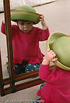 18 month old toddler girl wearing hat looking at self in mirror recognizing self vertical