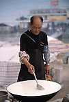 Man cooking porridge-like brew in open air; near docks on the Yangtze River; Fuling, China, Asia; commerce; food; 041803