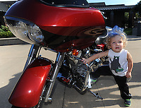 NWA Democrat-Gazette/ANDY SHUPE<br /> Spears Harris, 2, checks out a motorcycle on display Wednesday, Sept. 23, 2015, during the first day of the annual First School Trike Rally at First United Presbyterian Church in Fayetteville. The event, which serves as a fundraiser for St. Jude's Children's Hospital, features bike riding, temporary tattoos, snow cones, a bike wash and demonstrations from the Fayetteville Police Department. Visit nwadg.com/photos to see more photographs from the morning.