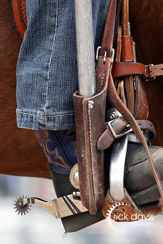 A cowgirl posts the colors during the Cheyenne Frontier Days Rodeo in Cheyenne, Wyoming. The leather pocket is used to hold the base of the flag pole solid along her stirrup while performing.