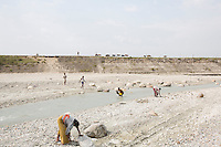 India – West Bengal: Former tea workers crushing stones along the Diana riverbed at Red Bank Tea Estate, in the Dooars region. The garden, which houses 888 workers out of a population of 5,000 people, has been closed since 2013, forcing its workers to resort to stonecrushing in order to survive.