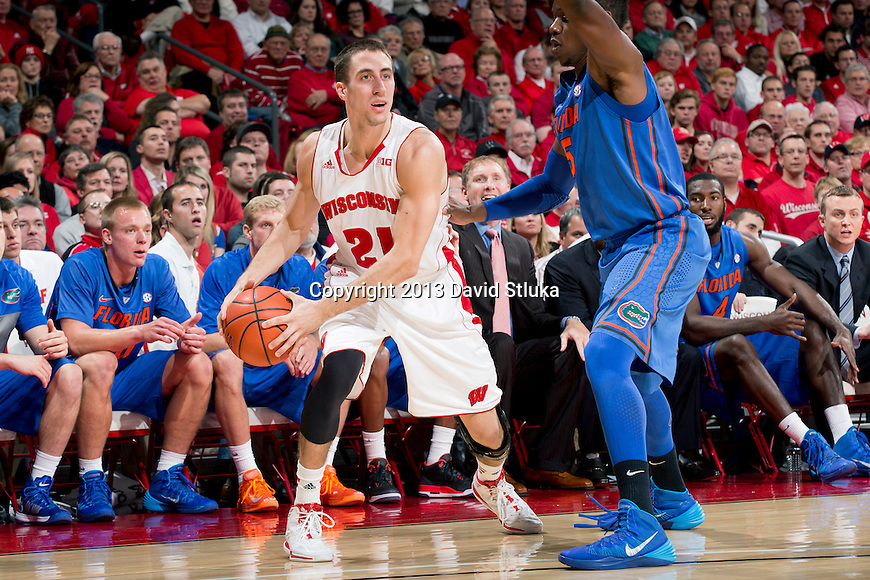 Wisconsin Badgers guard Josh Gasser (21) handles the ball against Florida Gators guard Scottie Wilbekin (5) during an NCAA college basketball game Tuesday, November 12, 2013, in Madison, Wis. The Badgers won 59-53. (Photo by David Stluka)